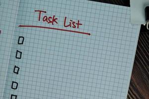 Aufgabenliste geschrieben in einem Buch isoliert auf Holztisch