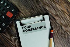 fcra Compliance geschrieben auf Papierkram isoliert auf Holztisch