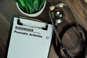 Diagnose - Psoriasis-Arthritis geschrieben auf Papierkram isoliert auf Holztisch