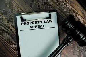 Eigentumsrechtsbeschwerde geschrieben auf Papierkram isoliert auf Holztisch