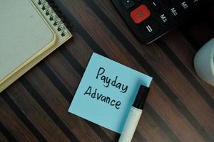 Zahltagvorschuss auf Haftnotiz isoliert auf Holztisch geschrieben