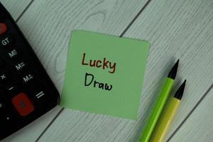 Glücksziehung auf Haftnotiz isoliert auf Holztisch geschrieben
