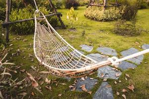 Hängematte aus Bambusgeflecht, die am Baum hängt, um sich im öffentlichen Garten zu entspannen foto