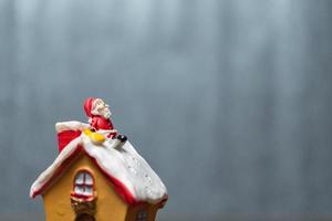 Miniatur-Weihnachtsmann, der auf einem Dach sitzt, Weihnachtslegende und frohe Feiertagskonzept