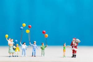 Miniatur-Weihnachtsmann und Kinder, die Luftballons, frohe Weihnachten und ein frohes neues Jahr-Konzept halten foto