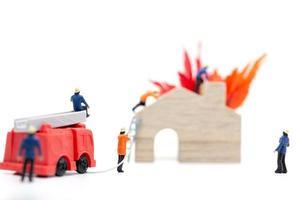 Miniatur-Feuerwehrleute, die sich um einen Brand in einem Holzhaus kümmern