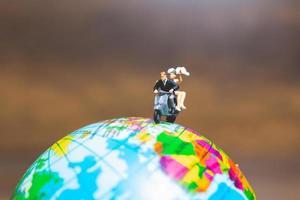 Miniaturpaar, das ein Motorrad auf einer Weltkugel reitet foto