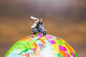 Miniaturpaar, das ein Motorrad auf einer Weltkugel reitet