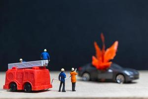 Miniatur Feuerwehrleute bei einem Autounfall, Autounfallkonzept
