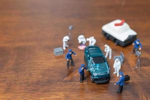 Miniaturpolizei und Detektiv, die um ein Auto stehen, Tatortuntersuchungskonzept