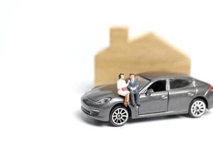 Miniaturmenschen, die auf einem Auto auf einem weißen Hintergrund sitzen
