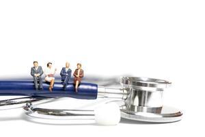 Miniaturmenschen, die auf einem Stethoskop auf einem weißen Hintergrund, Gesundheitskonzept sitzen foto