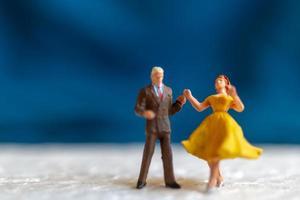 Miniaturpaar tanzt auf einer Etage, Valentinstagskonzept