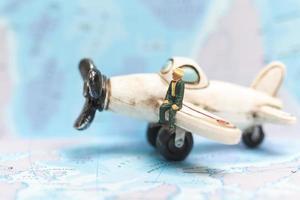 Miniaturperson, die auf einem Flugzeug mit einem Weltkartenhintergrund sitzt, Reisekonzept foto
