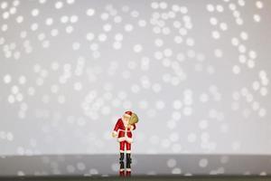 Miniatur-Weihnachtsmann, der eine Tasche auf einem Bokeh-Hintergrund, frohe Weihnachten und ein frohes neues Jahr-Konzept trägt.