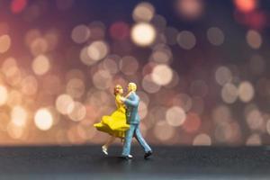 Miniaturpaar tanzt mit einem Bokeh-Hintergrund, Valentinstagskonzept