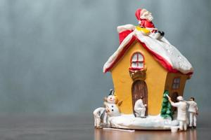 Miniaturmenschen, die ein Haus und einen Weihnachtsmann malen, die auf dem Dach sitzen, frohe Weihnachten und frohe Feiertagskonzept