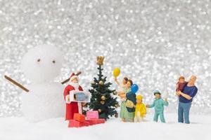 Miniatur-Weihnachtsmann und Kinder mit einem Schneehintergrund, Weihnachten und ein frohes neues Jahr-Konzept foto