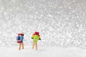 Miniatur-Rucksacktouristen, die auf einem Schneehintergrund, Winterkonzept gehen foto