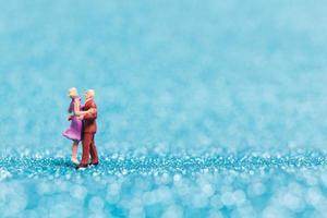 Miniaturpaar tanzt auf blauem Glitzerhintergrund, Valentinstagkonzept