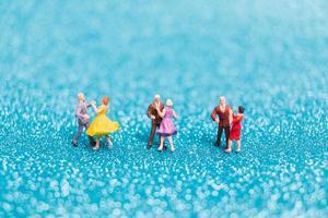 Miniaturpaare tanzen auf blauem Glitzerhintergrund, Valentinstagkonzept
