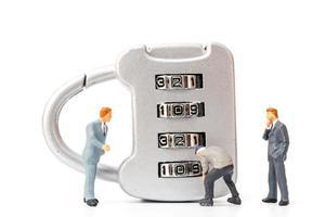 Miniaturperson, die an einem Zahlenschloss arbeitet foto
