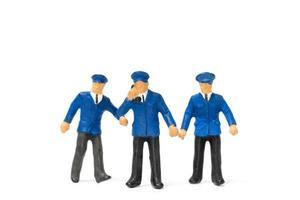 Miniaturpolizisten, die lokalisiert auf einem weißen Hintergrund stehen