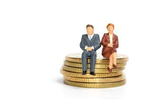 Miniatur-Geschäftsleute sitzen auf einem Stapel Münzen, Geld und Finanzkonzept