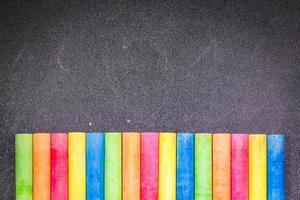 Reihe regenbogenfarbener Kreide auf einer Tafel foto