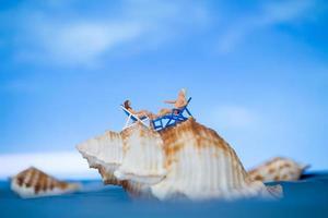 Miniaturmenschen, die auf einer Muschel mit einem Hintergrund des blauen Himmels, Sommerferienkonzept sonnenbaden