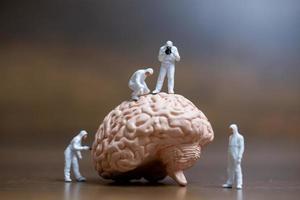 Miniaturwissenschaftler, die das Konzept des menschlichen Gehirns, der medizinischen Gesundheitsversorgung und des chirurgischen Arztes beobachten und diskutieren foto
