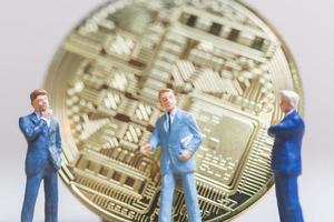 Miniaturgeschäftsleute, die vor einer Bitcoin-Kryptowährungsmünze stehen, Geschäftskonzept