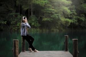 Frau, die nahe auf einem Dock entspannt, das Musik hört foto