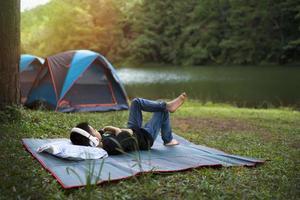 Junge, der sich nahe einem See entspannt, der Musik hört foto
