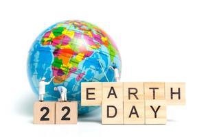 Miniaturmaler, die auf einem Globus auf einem weißen Hintergrund malen, Tag der Erde Konzept foto