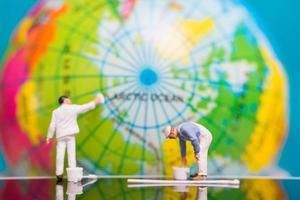Miniaturmaler malen auf einem Globus, Tag der Erde Konzept foto