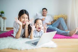 glückliches Familienvideo, das auf einem Laptop chattet foto