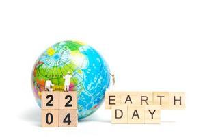 Miniaturmaler, die auf einem Globus mit Holzklötzen malen, die Erdtag 22 04 auf einem weißen Hintergrund, Erdtagkonzept zeigen foto