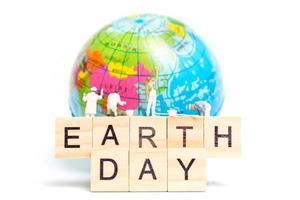 Miniaturmaler, die auf einem Globus mit Holzklötzen malen, die den Tag der Erde auf einem weißen Hintergrund, Tag des Tages der Erde zeigen foto