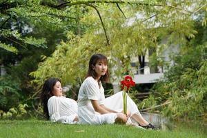 zwei Frauen, die sich in einem Park mit Blumen entspannen foto