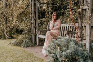 Frau sitzt auf einer Parkbank in einem Kleid foto