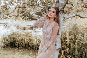 Frau, die ein Spitzenkleid gegen einen Baum trägt foto