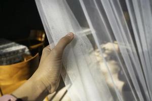 Frauenhand auf dem Vorhang foto