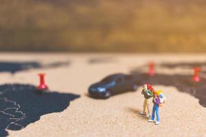 Miniaturreisende, die auf einer Weltkarte spazieren gehen, reisen und das Weltkonzept erkunden foto
