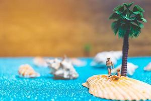Miniaturmenschen, die Badeanzüge tragen, die auf einer Muschel mit einem glitzernden Hintergrund entspannen foto