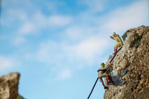 Miniaturwanderer, die auf ein Felsen-, Sport- und Freizeitkonzept klettern foto