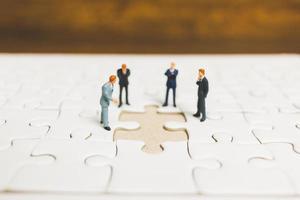 Miniaturgeschäftsleute, die auf Stichsägen mit einem hölzernen Hintergrund, Geschäftskonzept stehen foto