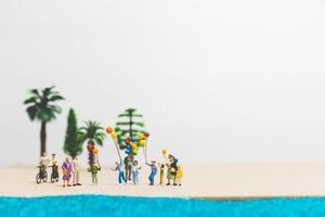 Miniaturmenschen, die Sommerferien am Strand genießen foto