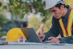 Ingenieur arbeitet an Tablet und Laptop vor Ort Bau foto