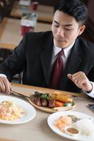 Geschäftsmann, der Steak in einem Restaurant isst foto